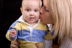 Young Beautiful Mom Kissing Baby on Cheek. Beautiful blond mom kissing her baby on the cheek.  Healthy 3-6 month old baby boy is looking straight at camera with Royalty Free Stock Image