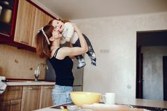 Mother with son. A young and beautiful mom is preparing food at home in the kitchen, along with her little son stock photography