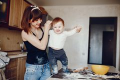 Mother with son. A young and beautiful mom is preparing food at home in the kitchen, along with her little son stock photos