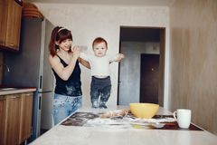 Mother with son. A young and beautiful mom is preparing food at home in the kitchen, along with her little son stock images