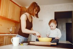 Mother with son. A young and beautiful mom is preparing food at home in the kitchen, along with her little son royalty free stock images