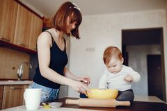Mother with son. A young and beautiful mom is preparing food at home in the kitchen, along with her little son stock photo