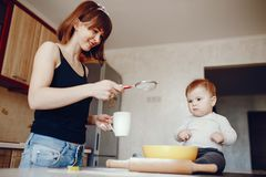 Mother with son. A young and beautiful mom is preparing food at home in the kitchen, along with her little son royalty free stock photo