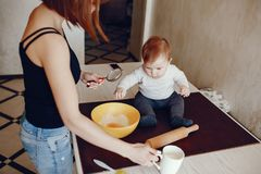 Mother with son. A young and beautiful mom is preparing food at home in the kitchen, along with her little son stock image