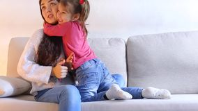 NYoung mother sitting on couch and gives small daughter phonen. Young beautiful mom sitting on couch with little daughter, child promises to be obedient and stock footage