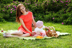 Young beautiful mother with a baby on a picnic Stock Images