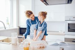Mother with daughter in the kitchen. A young and beautiful mother in a blue shirt and apron is preparing dinner at home in the kitchen, along with her little royalty free stock image