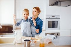Mother with daughter in the kitchen. A young and beautiful mother in a blue shirt and apron is preparing dinner at home in the kitchen, along with her little royalty free stock photos