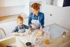 Mother with daughter in the kitchen. A young and beautiful mother in a blue shirt and apron is preparing dinner at home in the kitchen, along with her little royalty free stock images