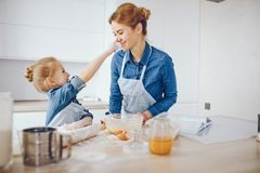 Mother with daughter in the kitchen. A young and beautiful mother in a blue shirt and apron is preparing dinner at home in the kitchen, along with her little royalty free stock photo