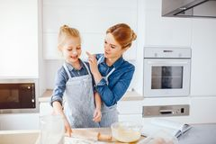 Mother with daughter in the kitchen. A young and beautiful mother in a blue shirt and apron is preparing dinner at home in the kitchen, along with her little stock photo