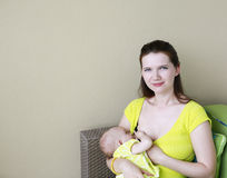 Young beautiful mother is breastfeeding baby. Nursing time on th Stock Images