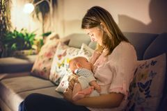 Young beautiful mother, breastfeeding her newborn baby boy. At night, dim light. Mom breastfeeding infant Stock Photography