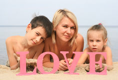Young beautiful mother with children lying on the beach with word Love Royalty Free Stock Photos