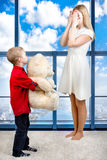 Young beautiful mother closed his eyes with his hands ,son gives mom a gift,a surprise, a big white Teddy bear. Spring concept of. Spring concept of family stock photo