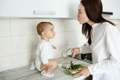Young beautiful mother cooking salad for breakfast and trying to kiss her little son while he looking at mom with. Interested expression Stock Photo
