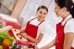 Young beautiful mother with daughter in aprons royalty free stock photos