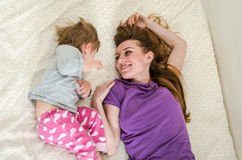 Young beautiful mother and daughter baby girl lying on the bed after waking up in the morning and sip, rested happy family.  Stock Photos