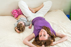 Young beautiful mother and daughter baby girl lying on the bed after waking up in the morning and sip, rested happy family Stock Photography