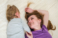 Young beautiful mother and daughter baby girl lying on the bed after waking up in the morning and sip, rested happy family.  Royalty Free Stock Photo