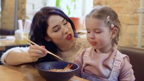 Young korean feeds her little daughter with a noodles in restaurant. Young beautiful mother feeds her little daughter with korean noodles. Happy family is stock footage