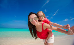 Young beautiful mother and her adorable daughter have fun at tropical beach Stock Image