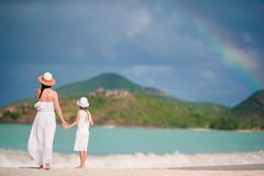 Young beautiful mother and her adorable little daughter have fun at tropical beach stock image