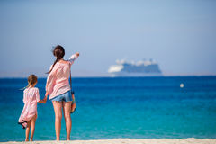 Young beautiful mother and her adorable little daughter at tropical beach looking at the sea Stock Photo