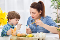 Young beautiful mother and her child  painting together eggs for Stock Photos