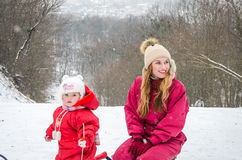 Young beautiful mother with her daughter Baby girl playing in the snow winter frosty day with sled on ski slope in the woods among Royalty Free Stock Photo