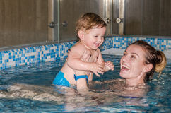 Young beautiful mother and her daughter happy family, play, fool around, and swimming in a pool of blue water, with positive emoti Royalty Free Stock Photos