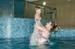 Young beautiful mother and her daughter happy family, play, fool around, and swimming in a pool of blue water, with positive emoti Stock Photography