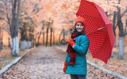 Girl in autumn city park in leaf fall. Young beautiful mother wi Royalty Free Stock Images