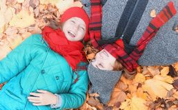 Girl in autumn city park in leaf fall. Young beautiful mother wi Royalty Free Stock Photography