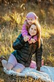 Young beautiful mother with her daughter on a walk on a sunny autumn day. They sit on a plaid on the grass close to each other, th stock image