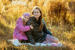 Young beautiful mother with her daughter on a walk on a sunny autumn day. They are sitting on a plaid on the grass, a daughter is stock photo