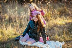 Young beautiful mother with her daughter on a walk on a sunny autumn day. Daughter is trying to put her hat on mother, they are la stock photo