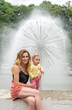 Young beautiful mother with her daughter walking in the park fountain that sprays water Stock Photos