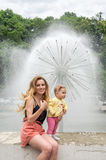 Young beautiful mother with her daughter walking in the park fountain that sprays water Stock Photo