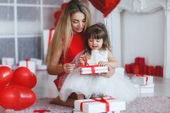 Happy mother and daughter parses gifts on Valentine`s Day. Young beautiful mother and her little daughter,dressed in a beautiful,festive and elegant dress stock photos