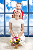 Young beautiful mother with her son and a bouquet of flowers. The child closed his mother`s eyes, surprise. Spring concept of fami. Spring concept of family stock image