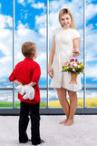 Young beautiful mother with her son and a bouquet of flowers. The child gives the mother a small Teddy bear, surprise.Spring conce. Spring concept of family royalty free stock images