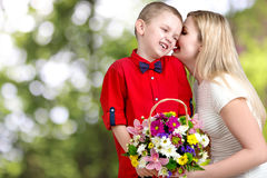 Young beautiful mother with her son.To whisper a secret in your ear. Woman and child with bouquet of flowers. Spring family holida. Spring family holiday concept stock photos