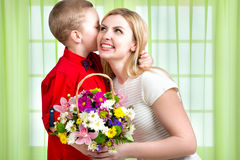 Young beautiful mother with her son.To whisper a secret in your ear. Woman and child with bouquet of flowers. Spring family holida. Spring concept of family stock photos