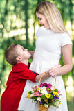 Young beautiful mother with her son.A woman and a baby boy with a bouquet,a basket of flowers. Spring concept of family vacation. Spring concept of family stock photography