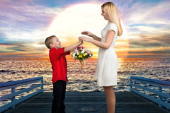 Young beautiful mother with her son.A woman and a baby boy with a bouquet,a basket of flowers. Spring concept of family vacation. Spring concept of family royalty free stock image