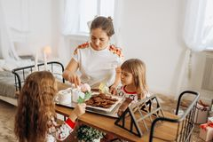 Young beautiful mother and her two charming little daughters sit stock images