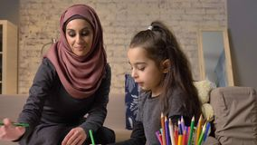 Young beautiful mother in hijab doing homework lessons, little daughter chooses color pencils, draws, children`s. Coloring, home comfort in the background stock footage