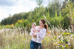 Young beautiful mother holding a baby girl wearing a pink dress in a meadow. On a sunny day royalty free stock images