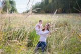 Young beautiful mother holding a baby girl wearing a pink dress in a meadow Stock Photos